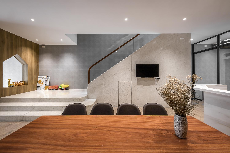 hình ảnh cận cảnh bàn ăn bằng gỗ, ghế ngồi màu đen, cạnh đó là khu vui chơi của trẻ ở bậc thềm cầu thang