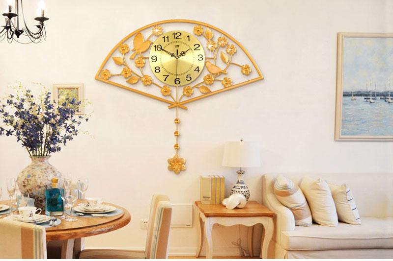 hình ảnh minh họa cho việc treo đồng hồ theo phong thủy với đồng hồ hình cánh quạt màu vàng giữa sofa phòng khách màu trắng và bàn ăn gỗ