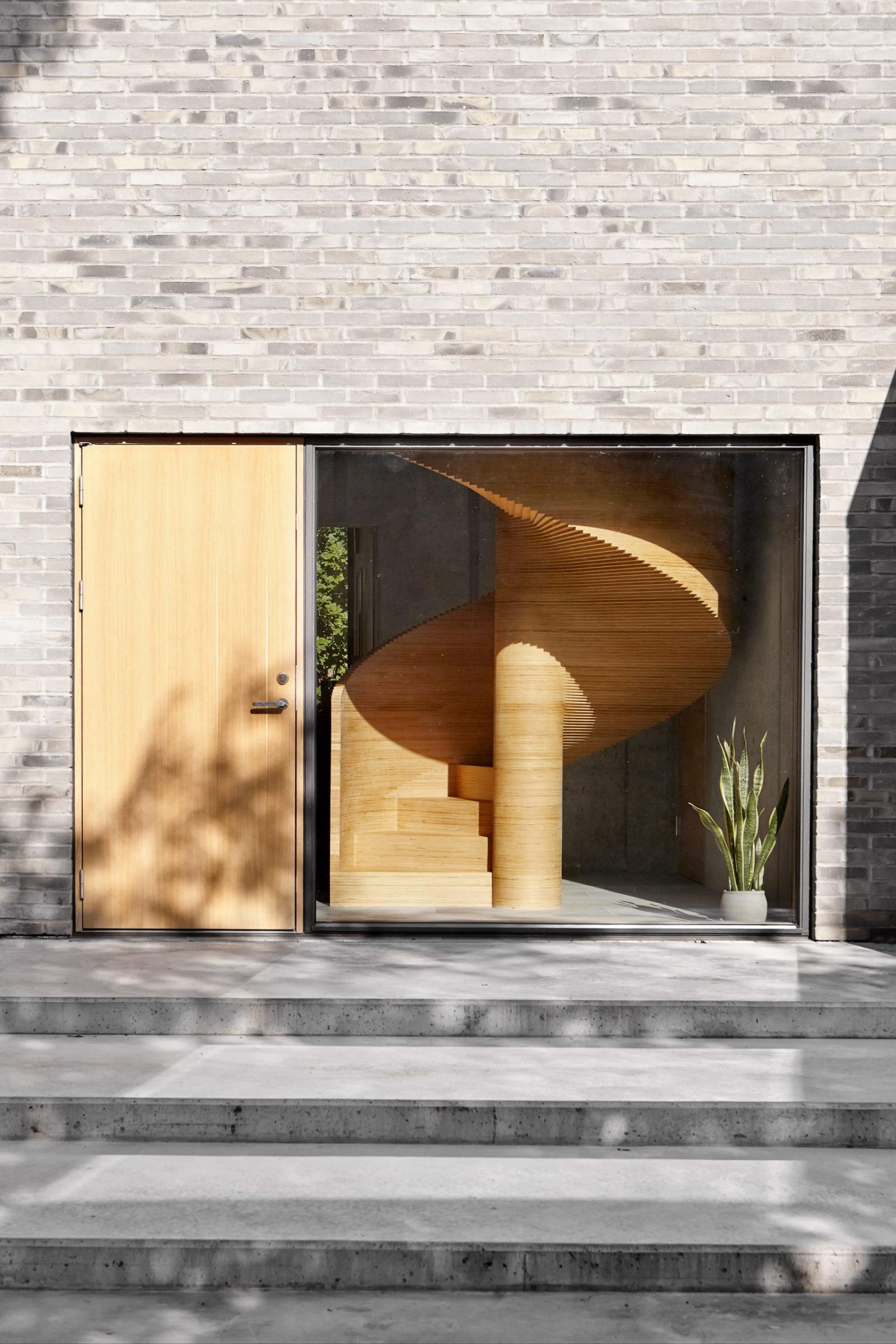 Cầu thang xoắc ốc làm từ ván ép CNC trở thành điểm nhấn kiến trúc của công trình. Đồng thời, chất liệu gỗ nâu vàng tương phản với bê tông trần, tạo cảm giác ấm áp.