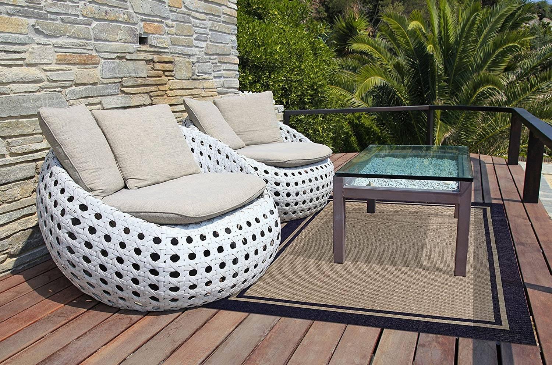 Cặp ghế đan màu trắng độc đáo là điểm nhấn của chỗ ngồi ngoài trời này.