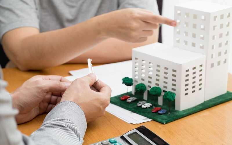 hình ảnh hai người đang ngồi cạnh mô hình tòa chung cư
