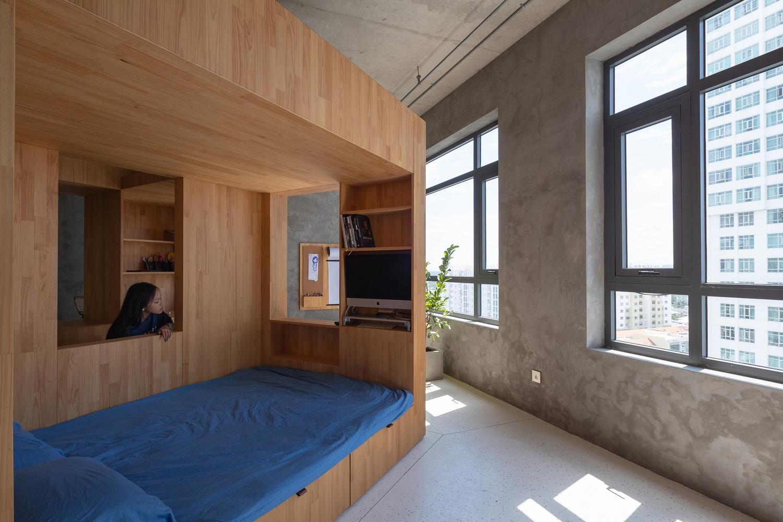 Trung tâm căn hộ 68m2 là khối hộp gỗ điêu khắc kích thước 3x3x2,2m - nơi đặt giường tầng, góc làm việc, học tập và kệ tủ lưu trữ.