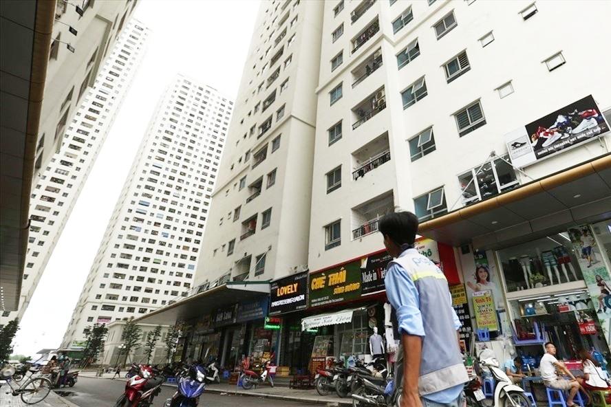 hình ảnh một người công nhân đang ngước nhìn lên khu nhà ở xã hội cao tầng