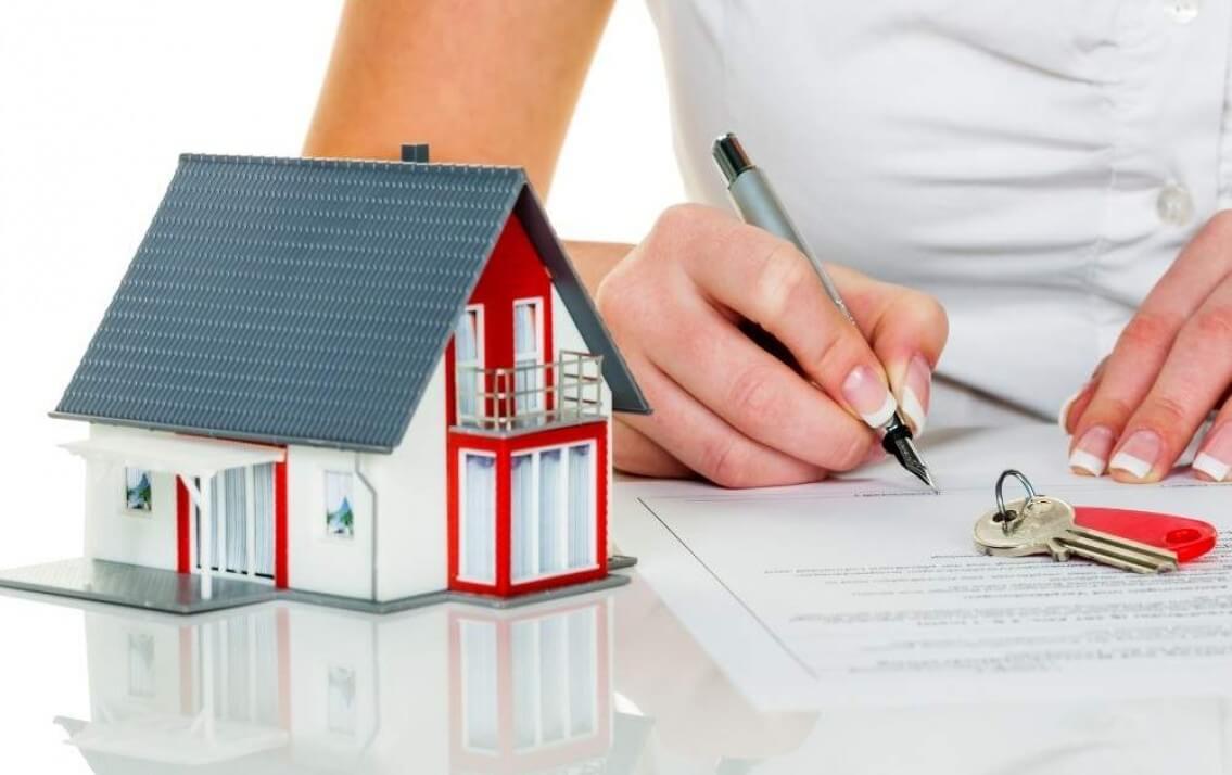 hình ảnh cận cảnh mô hình ngôi nhà, bàn tay ký hợp đồng minh họa cho thủ tục sang tên sổ hồng chung cư