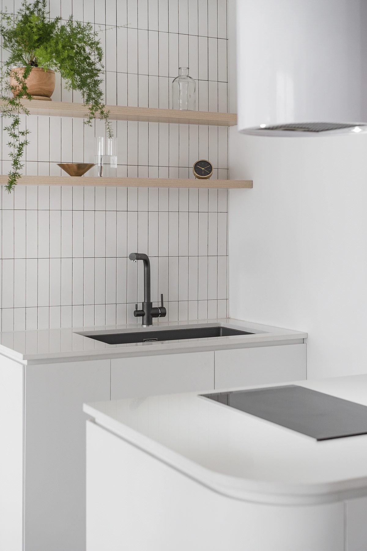 Kệ gỗ, tường ốp gạch thẻ, chậu cảnh xanh mát và một vài món đồ nhỏ xinh tạo vẻ sinh động, hút mắt cho không gian bếp nấu.