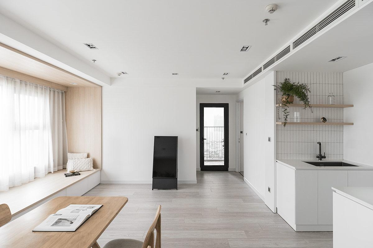 toàn cảnh phòng bếp ăn vầ ghế ngồi bên cửa sổ căn hộ tối giản