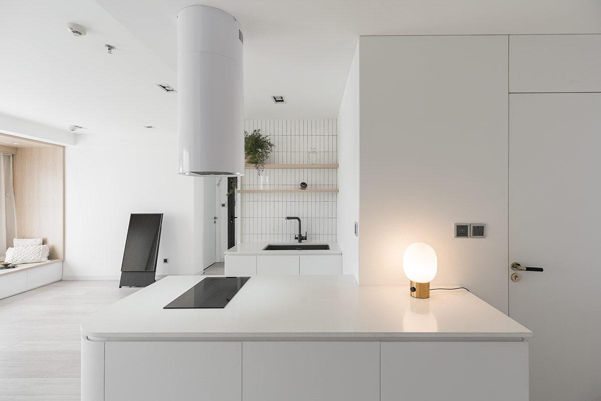 Bán đảo bếp nằm ở trung tâm với đèn chiếu sáng tạo điểm nhấn ấm áp.