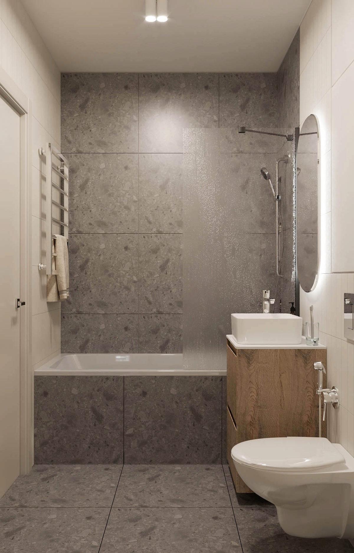 hình ảnh toàn cảnh phòng tắm với bồn tắm sứ, vòi sen, tường và sàn ốp gạch granite màu xám