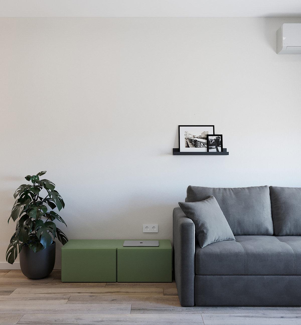 Cạnh ghế sofa màu xám thanh lịch là kệ ngồi màu xanh lá mát mắt - nơi đặt máy vi tính, tạp chí hoặc bộ sạc điện thoại.