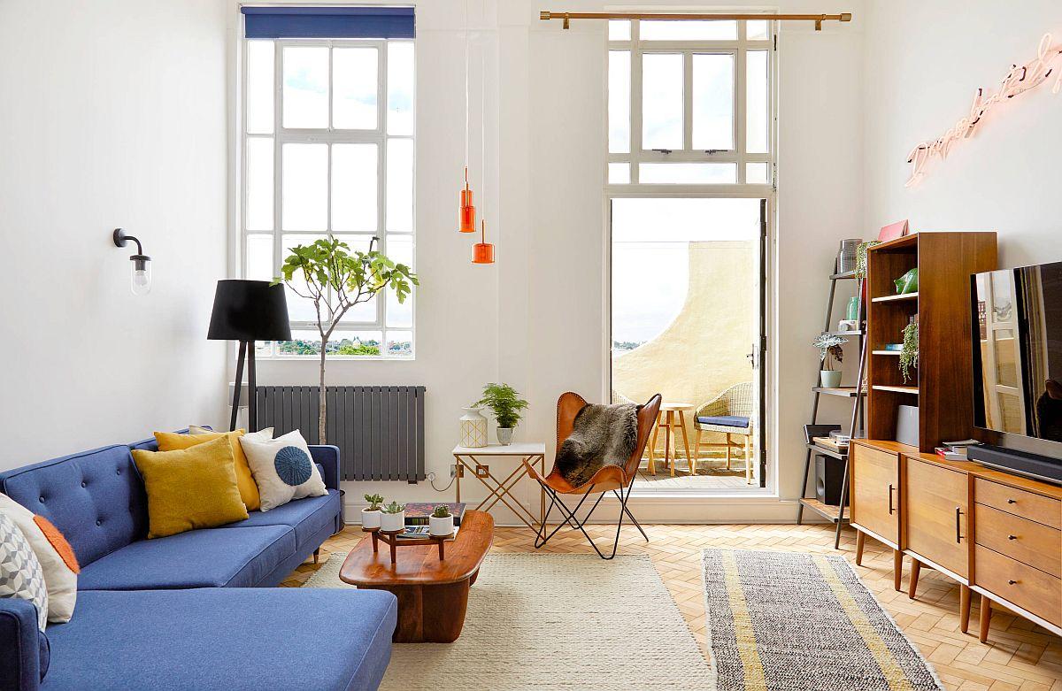 Phòng khách phong cách hiện đại giữa thế kỷ với ghế sofa màu xanh dương, gối tựa màu vàng tạo điểm nhấn sinh động, tràn đầy sức sống.