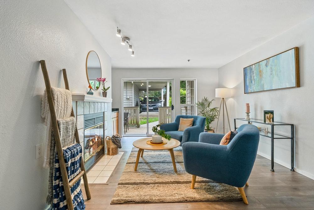 hình ảnh toàn cảnh phòng khách với sofa màu xanh dương, thang lưu trữ, gương tròn, cây xanh