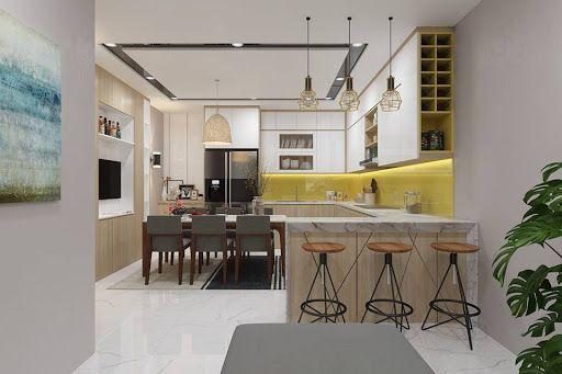 Bếp nấu và phòng ăn được tích hợp trong cùng một mặt sàn, có thêm bar mini nhỏ xinh. Tường chắn ốp gạch màu vàng mù tạt tạo điểm nhấn ấm áp.