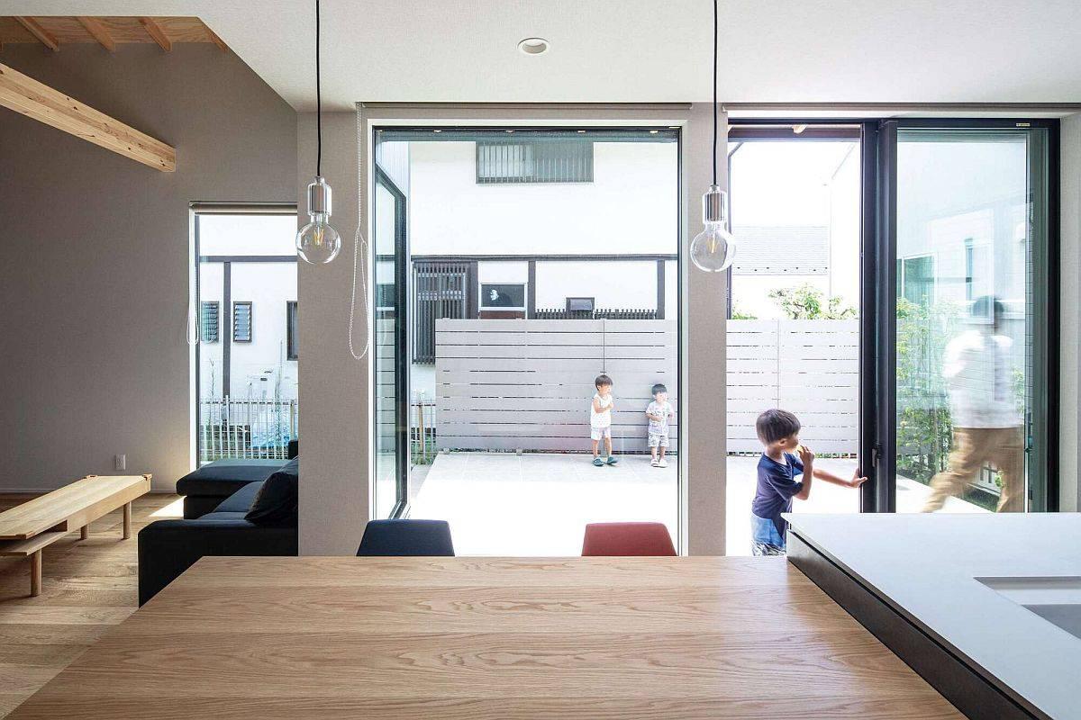 Nội thất gỗ màu trung tính cùng hệ tường và cửa kính thông minh mang đến vẻ đẹp đương đại, cuốn hút cho ngôi nhà.