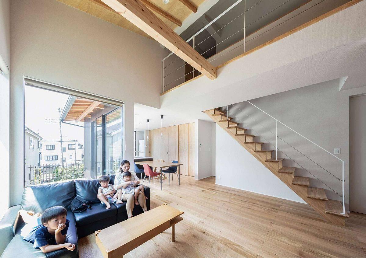 Thiết kế thông tầng, tường màu trắng kết hợp cùng ánh sáng tự nhiên tạo cảm giác phòng khách ngôi nhà như cao gấp đôi so với thực tế.