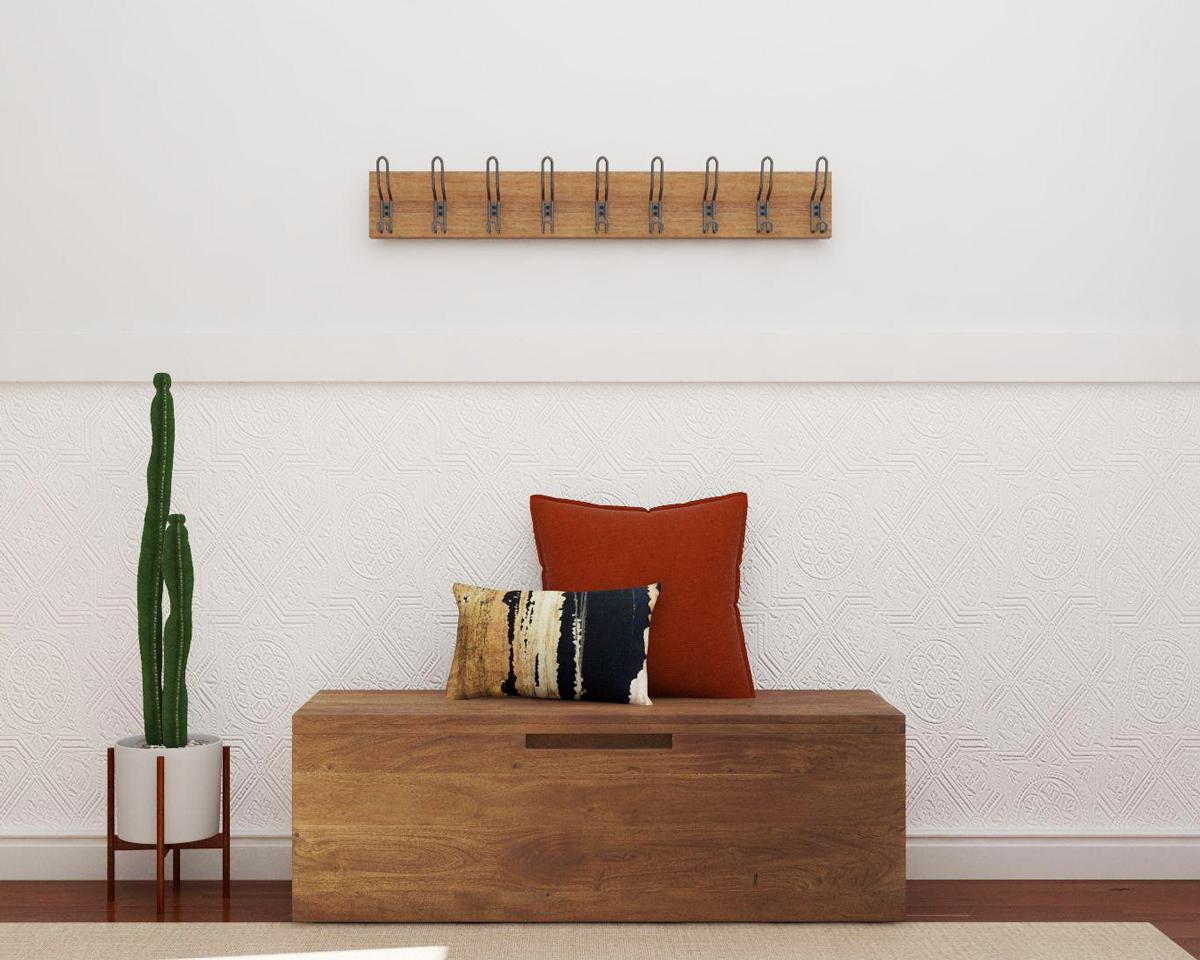 Lối vào nhà phong cách tối giản chỉ với móc treo tường, bệ gỗ tích hợp lưu trữ và chậu cây xương rông tạo điểm nhấn mát mắt.