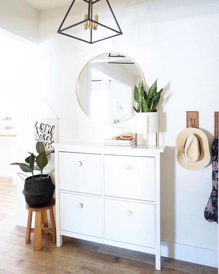 Trang trí lối vào nhà sang trọng với điểm nhấn là chiếc đèn chùm kiểu dáng hình học lạ mắt cùng chất liệu đồng sáng bóng, hài hòa với khung gương treo tường.