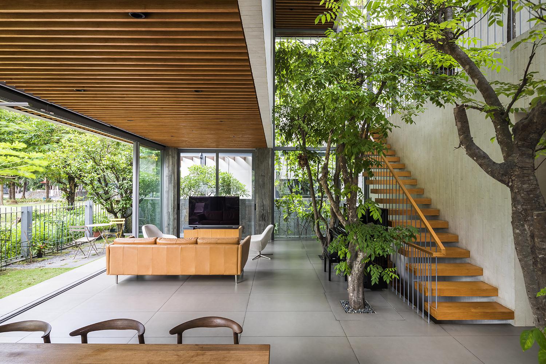 Ở tầng trệt, phòng khách phong cách mở, hướng nhìn ra công viên. Tầng trên cùng như một phòng gia đình phủ đầy cây xanh.