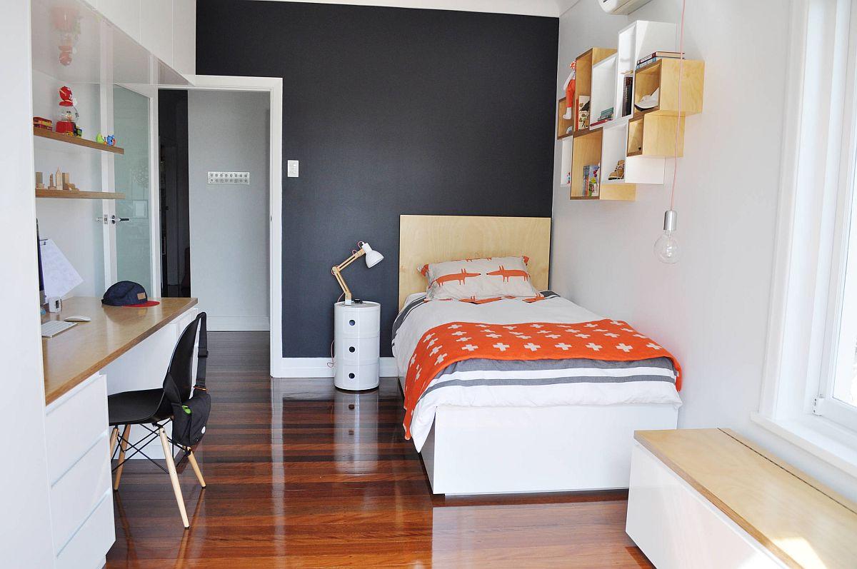 Phòng ngủ bé trai hiện đại với bức tường đầu giường sơn màu xám đen ấn tượng, bàn học - giá sách gọn gàng, cùng với đó là ghế ngồi thư giãn bên cửa sổ ngập nắng.