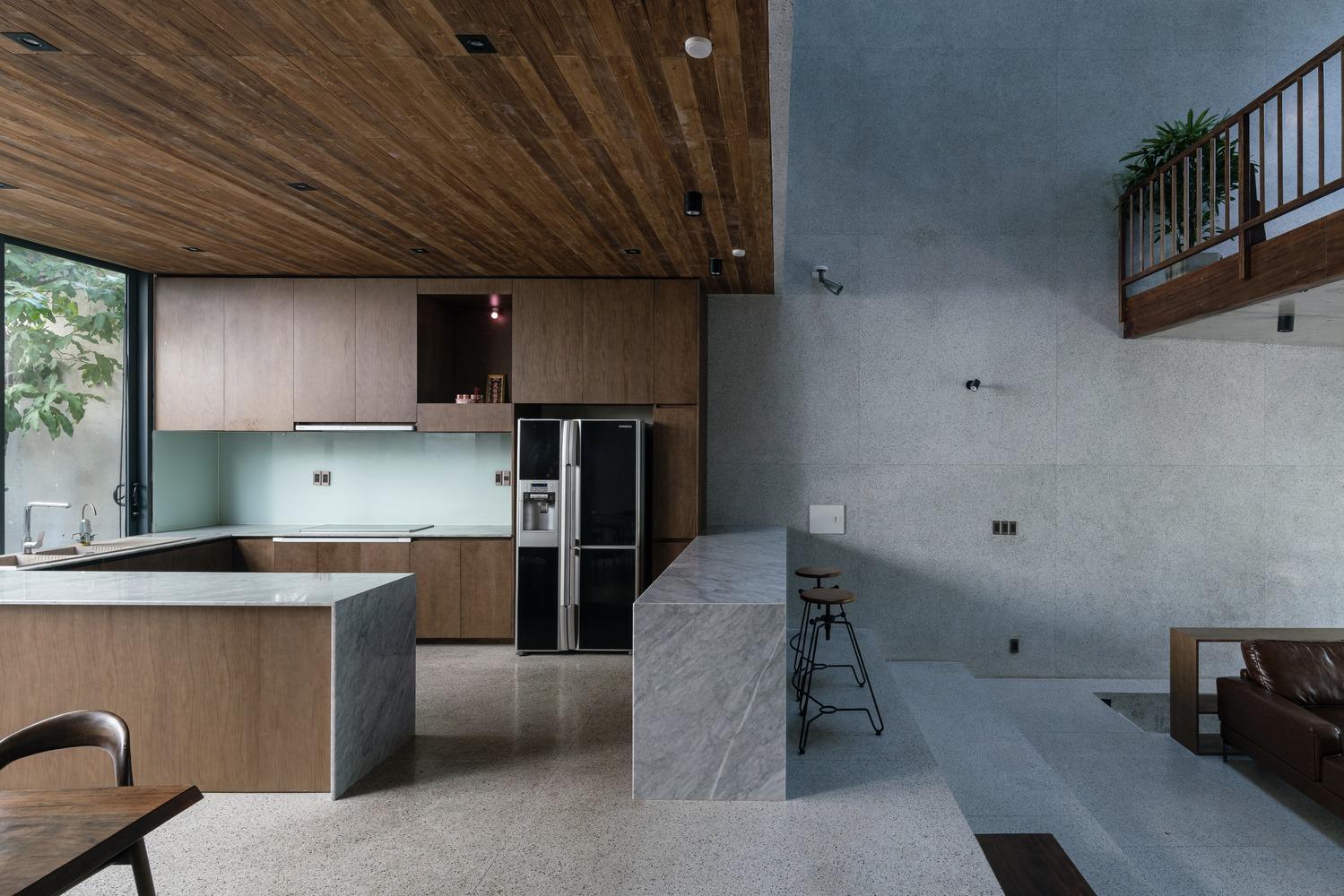 Phòng bếp rộng rãi với trần ốp gỗ, tường bê tông xám