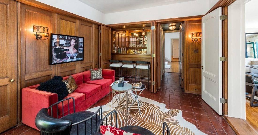 phòng khách với sofa màu đỏ, thảm trải ngựa vằn, tường ốp gỗ
