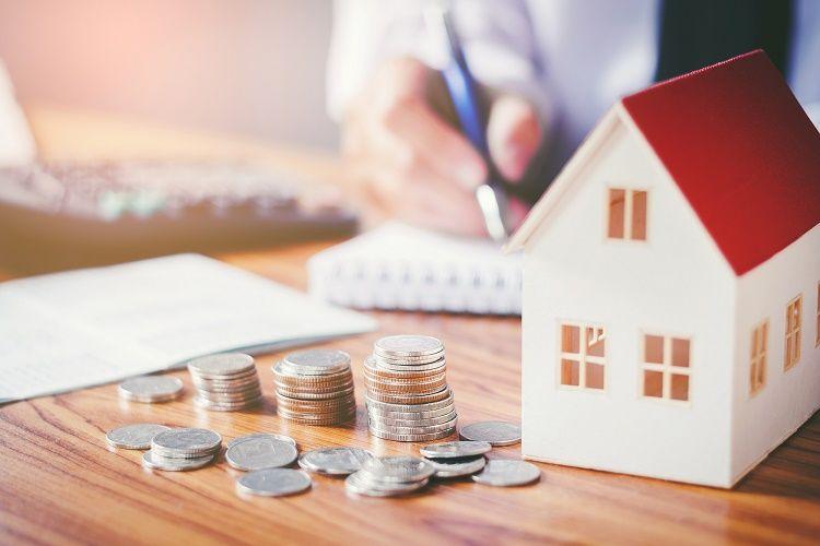hình ảnh các cọc tiền xu xếp bên cạnh mô hình ngôi nhà mái màu đỏ, phía sau là hình ảnh người ngồi viết