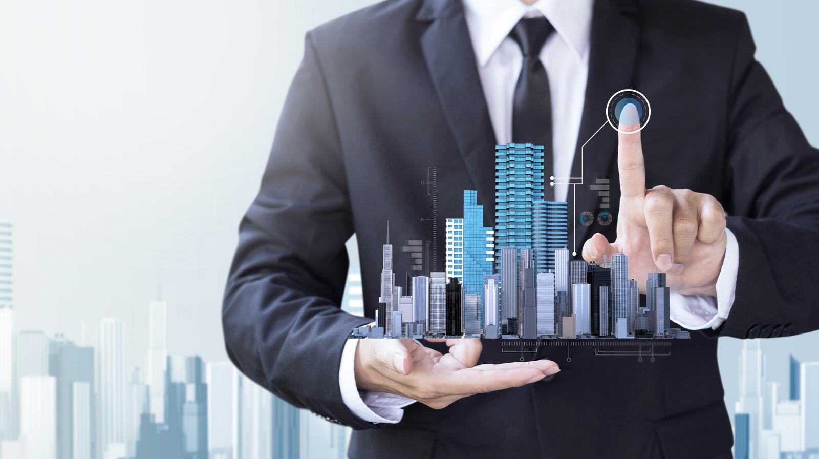 hình ảnh người đàn ông mặc vest đen, tay nâng mô hình khu đô thị