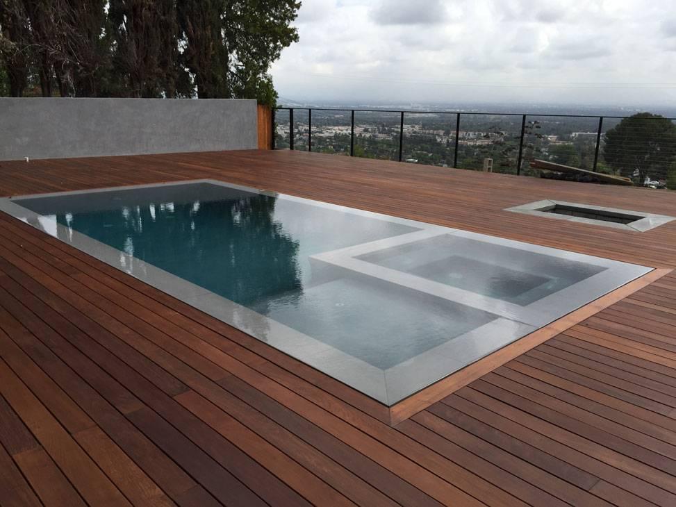 Sàn bể bơi tràn trông thật hút mắt với sự kết hợp giữa chất liệu gỗ - bê tông.