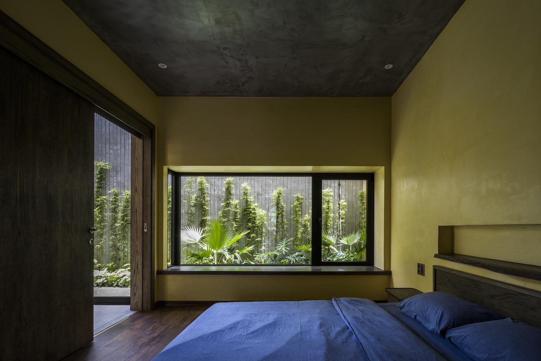 Kiến trúc sư thiết kế ghế ngồi thư giãn bên cửa sổ kính, hướng nhìn ra khu vườn xanh tốt.