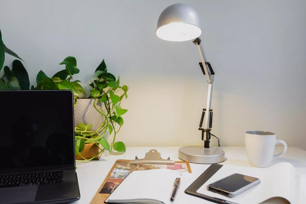 hình ảnh bàn làm việc với đèn bàn có khớp điều chỉnh, máy tính, sách vở, giấy tờ
