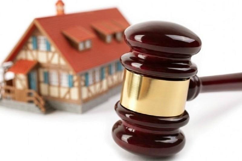 hình ảnh cận cảnh búa pháp luật, xa xa hình ảnh ngôi nhà