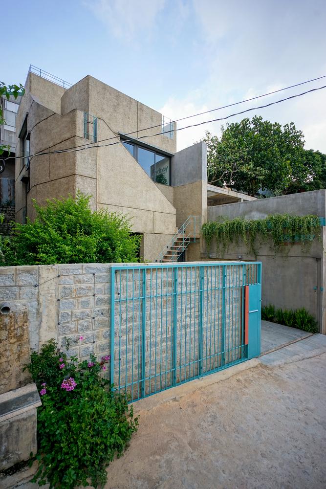 Ngôi nhà được bao bọc bởi những bức tường đá màu xám mộc mạc. Cổng sắt sơn màu xanh da trời tạo điểm nhấn sinh động, dịu mắt.