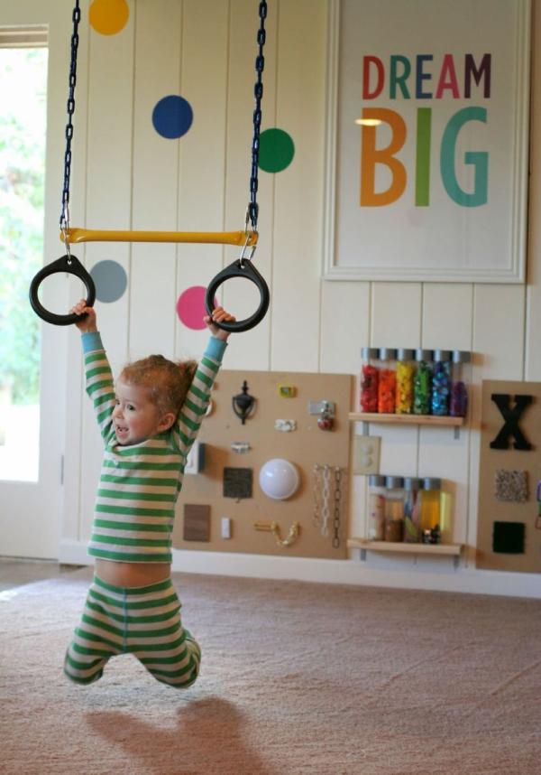 Bạn có thể biến phòng chơi của trẻ thành một phòng tập thể dục. Trong phòng chơi này, niềm vui tràn ngập khắp mọi nơi: Một bức tường dành riêng cho leo núi, xích đu và những chiếc vòng treo lủng lẳng trên trần nhà.